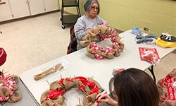 Women making a holiday wreath