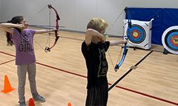 Two kids holding their bows shooting arrows at a target.